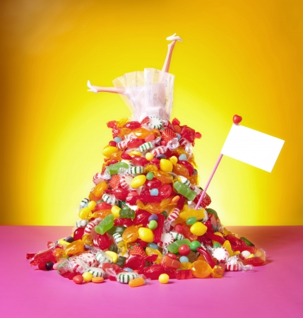 A doll in a white wedding gown sits on top of a mountain of candy with text space  photo