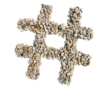 A hashtag symbol made of pebbles against a white background  photo