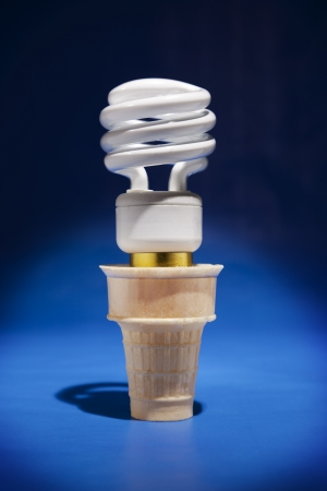 A compact flourescent light bulb sticks out of an ice cream cone in a spotlight
