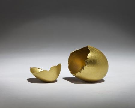 Cracked open golden egg in the spotlight photo