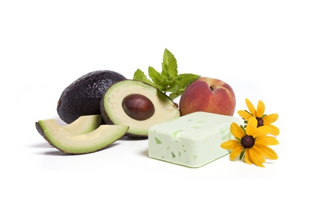 A sliced avocado and peach and green bar of hand made soap against a white background