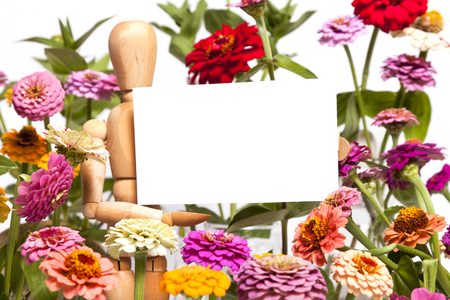 A Wooden Mannequin Holds Blank Sign around Flowers Banco de Imagens