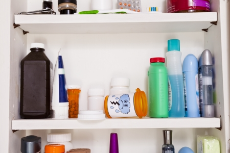An empty pill bottle with a frowny face lies on a shelf in a medicine cabinet.