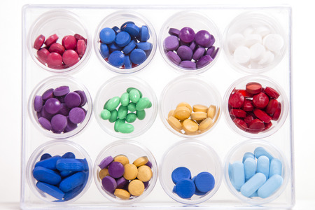 molly: A display of pills in circular containers stacked in rows and columns against a white background. Stock Photo