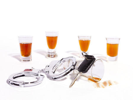 A still life of shot glasses, car keys and police handcuffs against a white background. Banco de Imagens