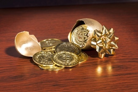A golden egg cracked open with gold coins coming out.