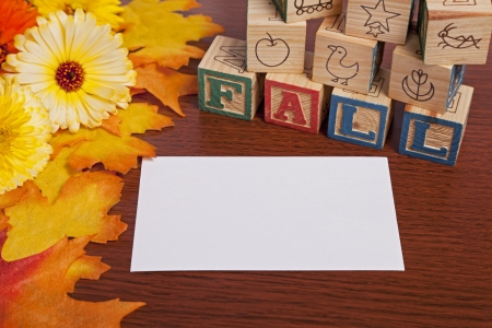 Copy space- Fall flowers and leaves create a frame on a wood board with the word fall spelled out by letter blocks and blank card for copy space.