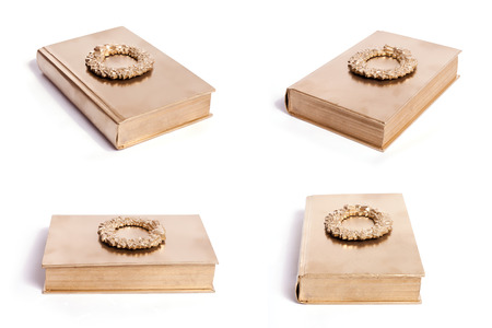 Four different angles of a gold book with a gold wreath on its cover.
