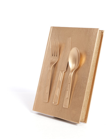 greys: A gold book with gold utensils on the cover against a white background.