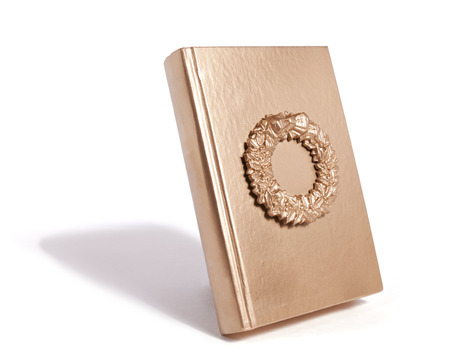 A gold wreath frame on the cover of a gold book.