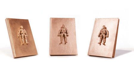 Three angles of a gold book with a gold soldier figurine attached to the cover.