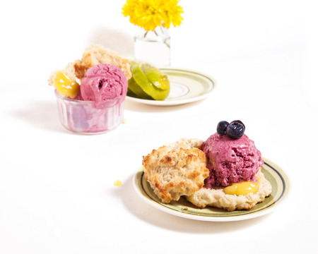 A scoop of homemade blueberry ice-cream on a buttermilk biscuit.