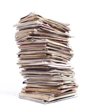 out dated: A large tall stack of magazines against a white background.