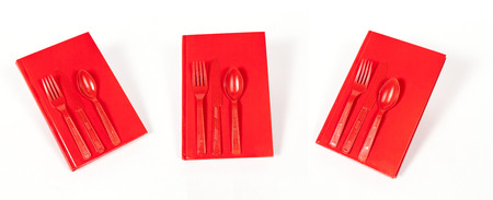 A red book with red utensils on the cover against a white background.