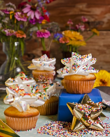 A group of freshly baked cupcakes with sprinkled ribbon icing.