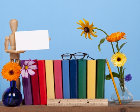 A  wooden mannequin  holds a card for copy space on a shelf with coloful books and flowers against a blue background.