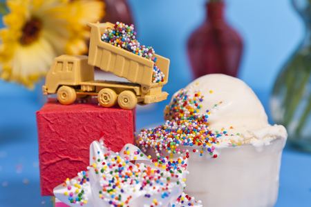 A toy truck dumps candy toppings onto a scoop of ice-cream.