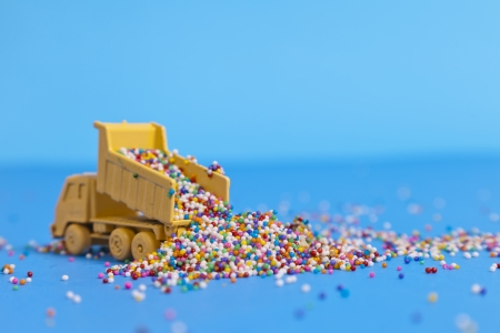 A toy truck pours sprinkles in to a pile.