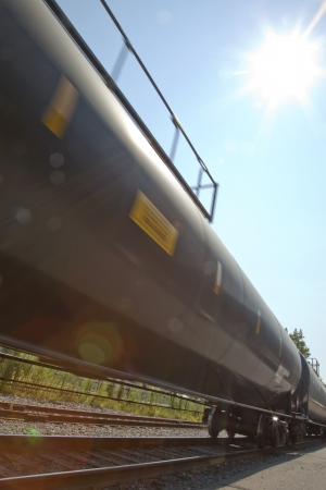 A train moving in the bright day sunlight with lens flare. Banco de Imagens