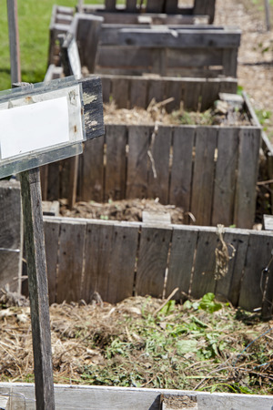 Several compost bins in a row at a community garden with blank sign post. Banco de Imagens