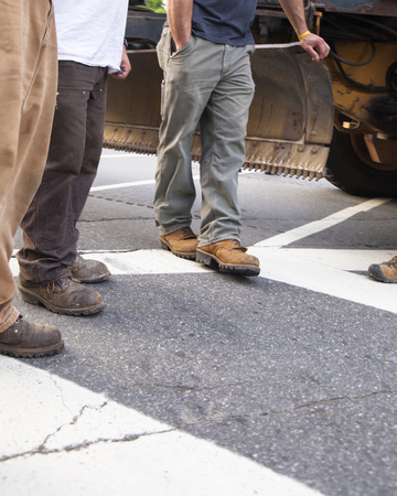Four men, cropped from the waist down, wearing workmens pants and boots stand around a piece of construction equipment on a road. Banco de Imagens