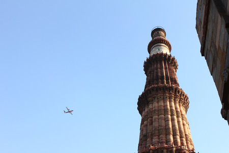 qutub minar with blue sky and plane