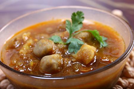 spicy chana masala, raw chickpeas around the bowl indian dish photo