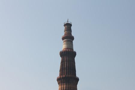 minar: qutub minar tower standing in blue sky   Stock Photo