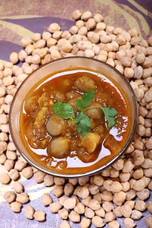 spicy chana masala, raw chickpeas around the bowlindian dish photo