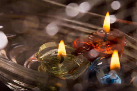 floating burning candles on water with bokeh photo