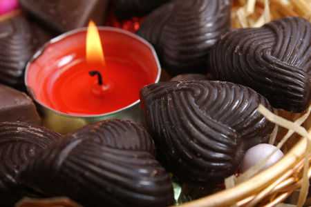 candle at center of home made chocolates - retro style Stock Photo