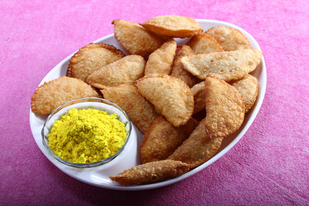 pista: gujia, indian traditional snacks for holi festival with yellow color in bowl