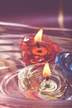 floating burning candles in glass aroma bowl - retro style photo
