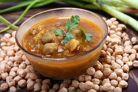 chana masala picante, garbanzos crudos de todo el taz�n con la cebolla verde plato indio