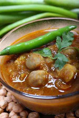 chaat: spicy chana masala, raw chickpeas around the bowl with green chilli topping, indian dish