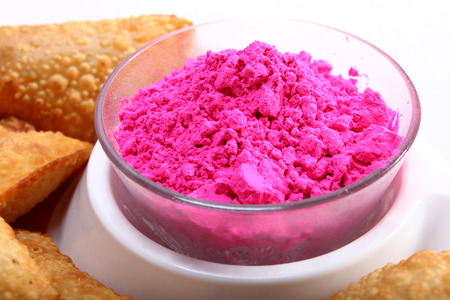 pink holi color in bowl with gujia