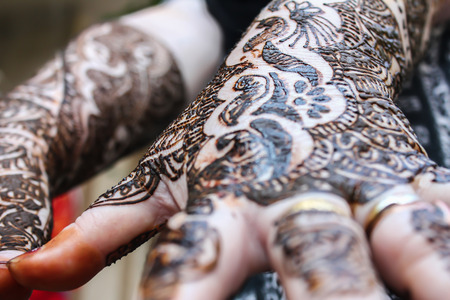 mehandi: designing henna is applied to the hands of a hindu bride