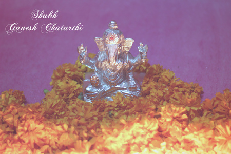 idol: oil lamp illuminated in front of lord ganesha idol with flowers and shubh ganesh chaturthi text