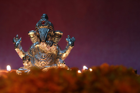 oil lamp illuminated in front of lord ganesha idol with flowers and space for text