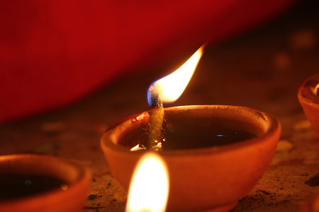 auspicious occasions: earthen lamp - diya on floor removes the darkness and spread illumination