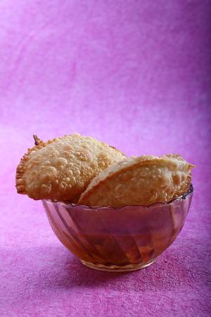 indian sweet snacks gujia in bowl, holi festival food