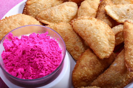 pista: Gujias, the traditional indian snack for holi festival with pink color in bowl