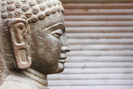 Closeup of side view of Gautaum Buddha statue in front of closed shutter Stock Photo