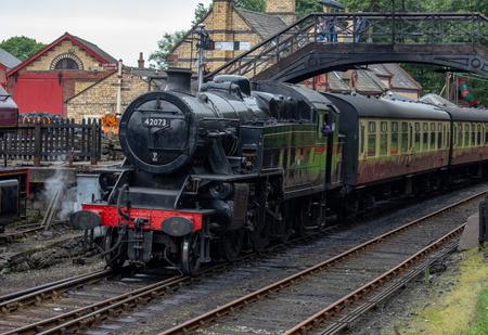 An old steam trains comes so a slow halt beneath a bridge Éditoriale