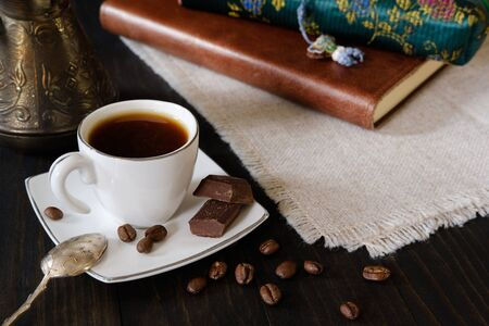 Small cup of black coffee with vintage teaspoon, turkish coffee pot and chocolate pieces on dark wooden background with diary and pencil case