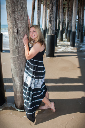 piling: Happy teen posing against pier piling.