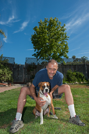pal: Man posing with Boxer puppy under blue sky
