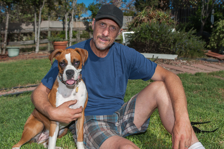 pal: Man holds his Boxer puppy close