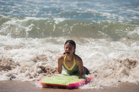 boogie: Girl child landing on sand as she rides the boogie board.