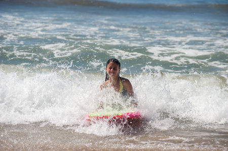 Girl child getting splashed in face while riding boogie board.
